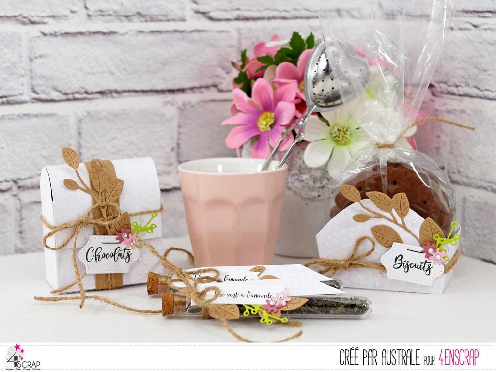 Ensemble gourmand composé de 2 boites et de deux étiquettes pour fioles de thé avec papier rose, feuillages en kraft et vert et quelques fleurettes roses.