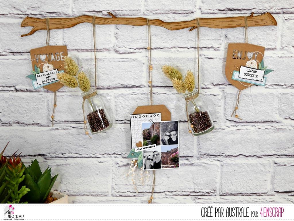 Home déco composé d'unr branche de bois sur laquelle a été placé 5 morceaux de ficelles pendantes avec des décorations, photos et feuillages.