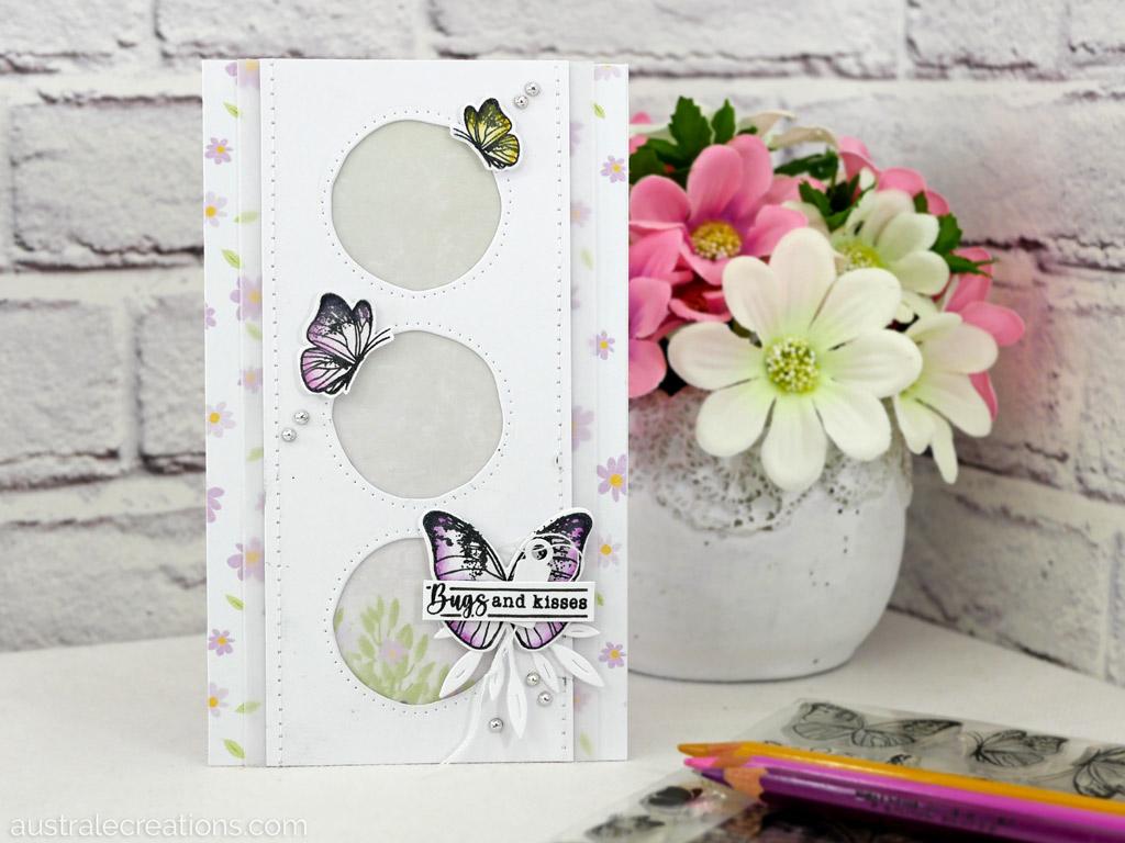 Carte d'amité en rose, mauve et jaune avec un papier de fond fleurettes, un trio de fenêtres rondes, papillons et feuillages.