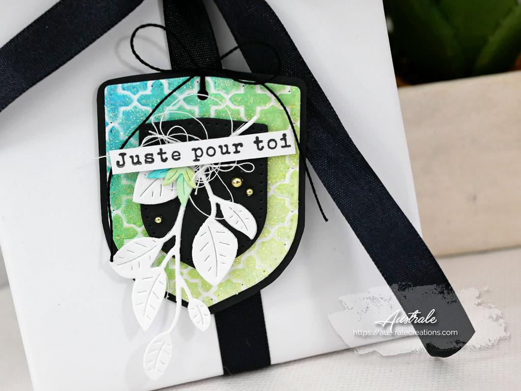 Etiquette cadeau avec fond distress et pochoir dans un combo de bleu, vert, jaune et noir.