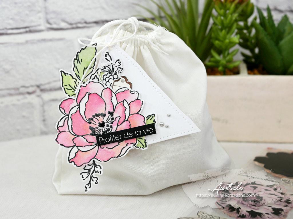 Étiquette cadeau en vert, rose, gris avec une jolie fleur, feuillages sur un fond de papier gris esperluette et triangles.