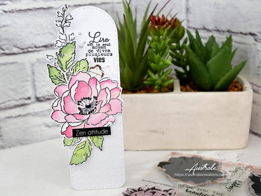 Marque page en vert, rose, gris avec une jolie fleur, feuillages sur un fond de papier gris esperluette et triangles.