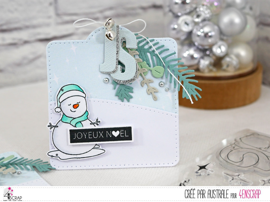 Etiquette cadeaux de Noël avec papier imprimé étoilé, colline enneigée, bonhomme de neige, feuillages d'hiver, initial du destinataire et quelques grelots argentés.