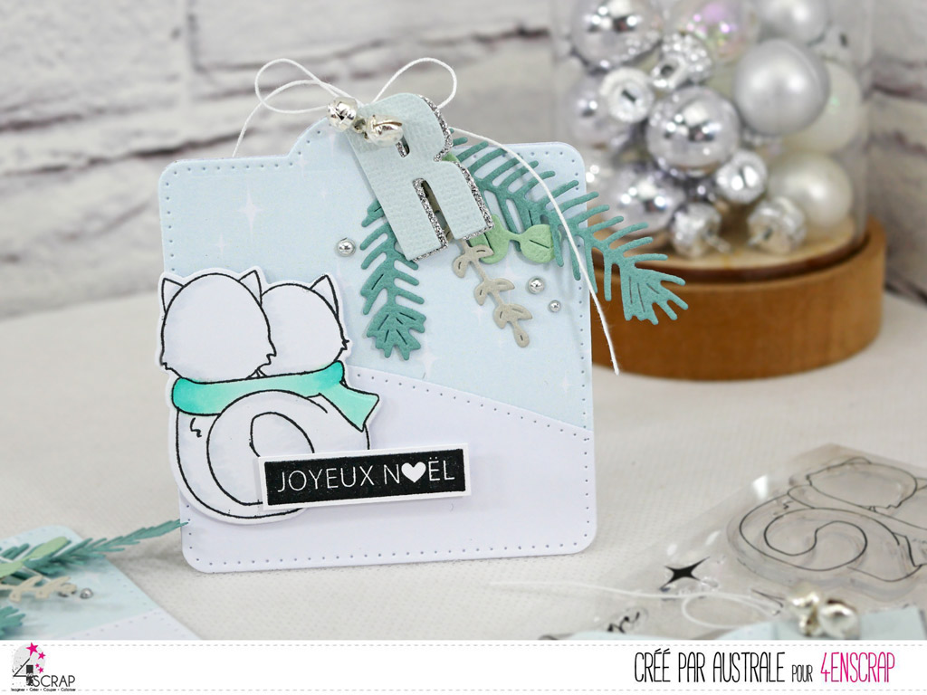Etiquette cadeaux de Noël avec papier imprimé étoilé, colline enneigée, couple de renards, feuillages d'hiver, initial du destinataire et quelques grelots argentés.