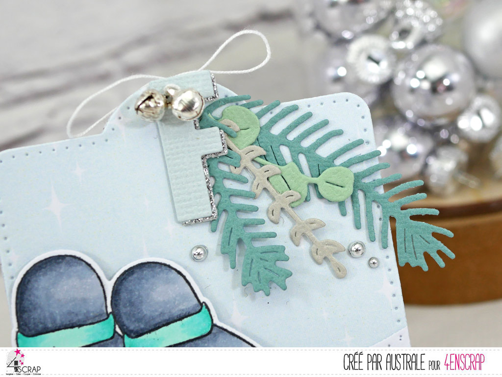 Etiquette cadeaux de Noël avec papier imprimé étoilé, colline enneigée, couple de pingouins, feuillages d'hiver, initial du destinataire et quelques grelots argentés.