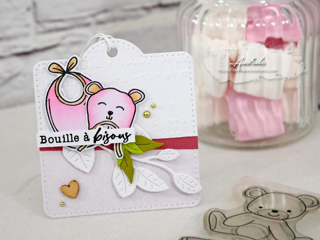 Etiquette cadeau de naissance avec fond embossé, feuillages bonnet et bavoir dans un combo en rose, marron et vert.