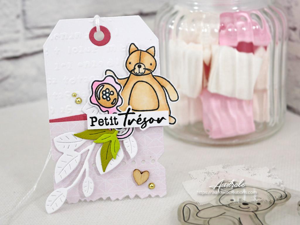 Etiquette cadeau de naissance avec fond embossé, feuillages et doudou dans un combo en rose, marron et vert.