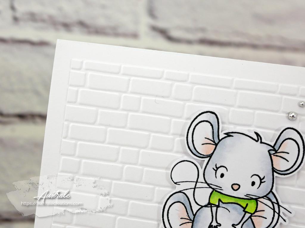 Carte d'anniversaire avec fond embossé mur de briques, petites souris et paquet cadeau dans un combo en vert, blanc et bleu.