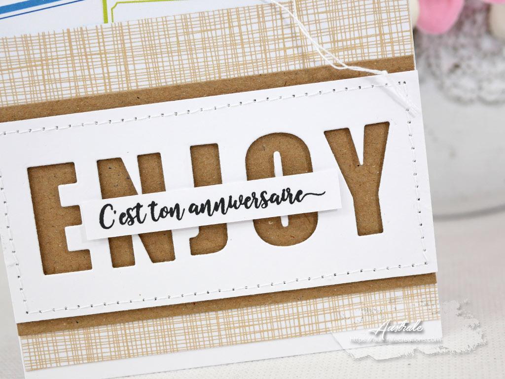 Carte d'anniversaire avec gros titre en transparence, étiquettes blanches et colorées et un papier de fond façon tissu dans un combo kraft, bleu et vert.