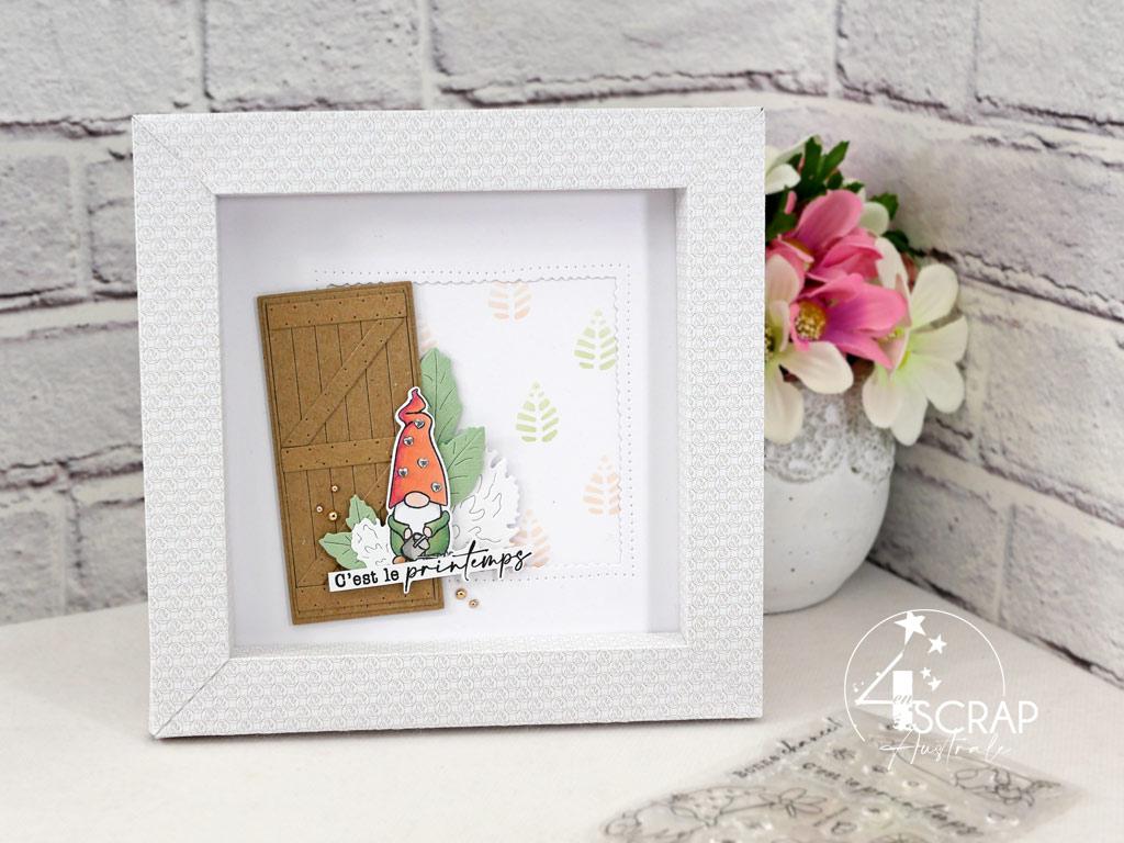 Cadre en papier imprimé avec fond réalisé au pochoir et à l'encre distress, porte de grange, feuillages et gnome de printemps.