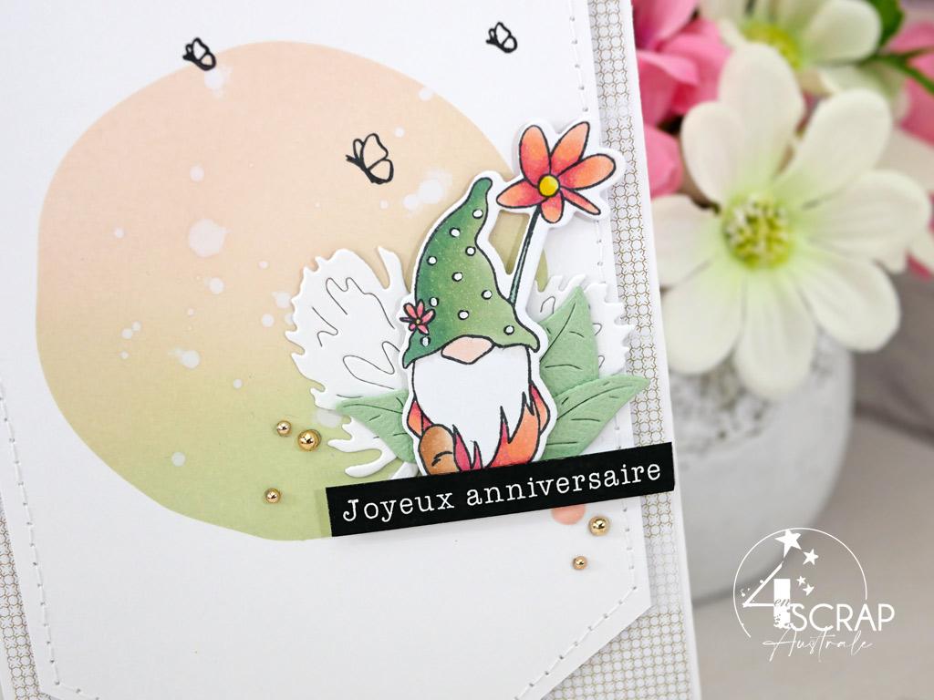 Carte d'anniversaire avec fond réalisé à l'encre distress et un cluster de feuillages, étiquette et lutin de printemps mis en couleurs aux feutres à alcool.
