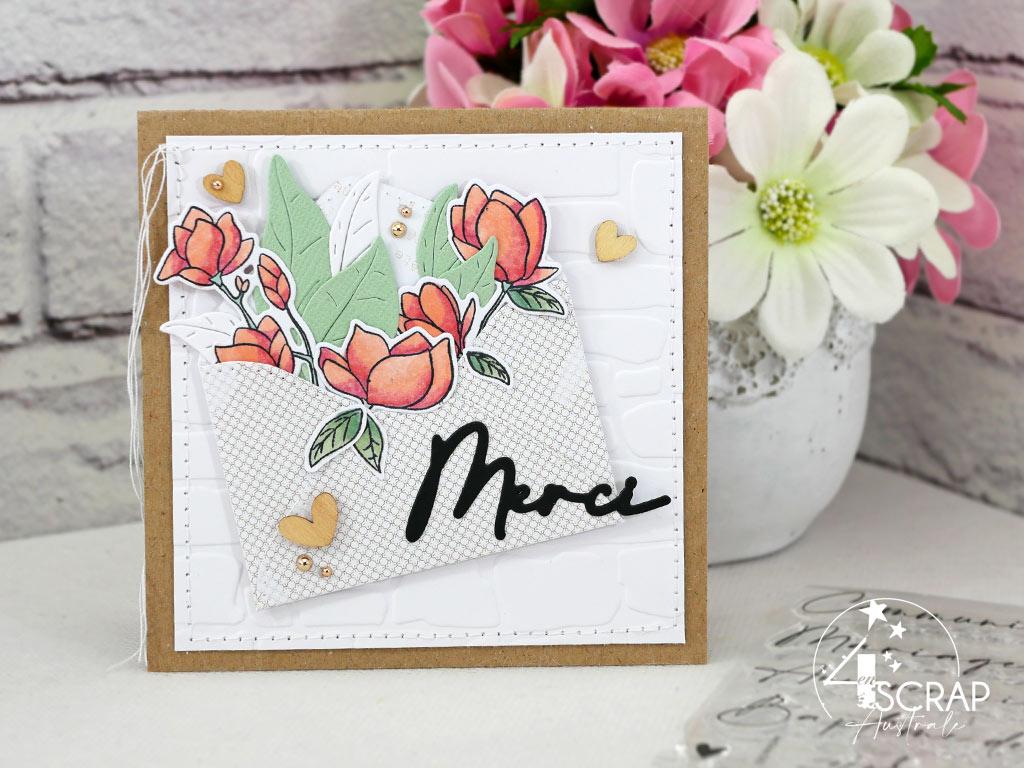 Carte de remerciement en rose, vert et kraft, mur de briques, enveloppe de fleurs et feuillages, petits cœurs en bois et une touche de couture.