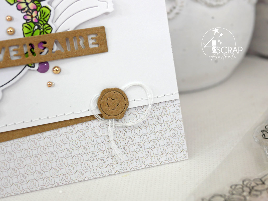 Carte d'anniversaire avec couronne de violettes, feuillages et grande étiquette dans un combo en kraft, mauve et vert.