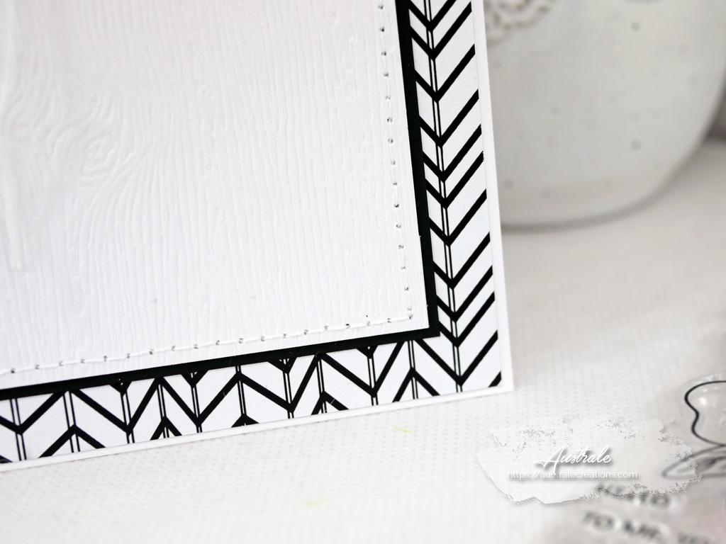 Carte d'anniversaire avec fond graphique noir, tampon fleurs à l'aquarelle, étiquette et quelques perles nacrées.
