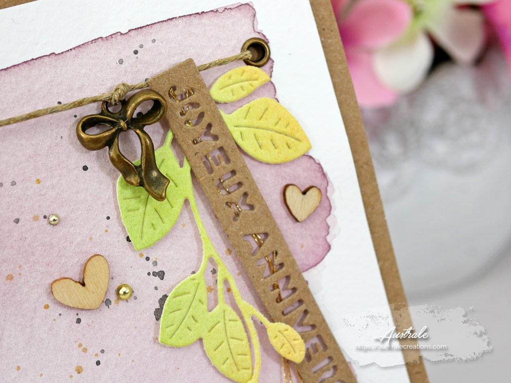 Carte dans des tons kraft, vieux rose et vert avec fond aquarelle, feuillage, étiquette, breloque et embelissements.