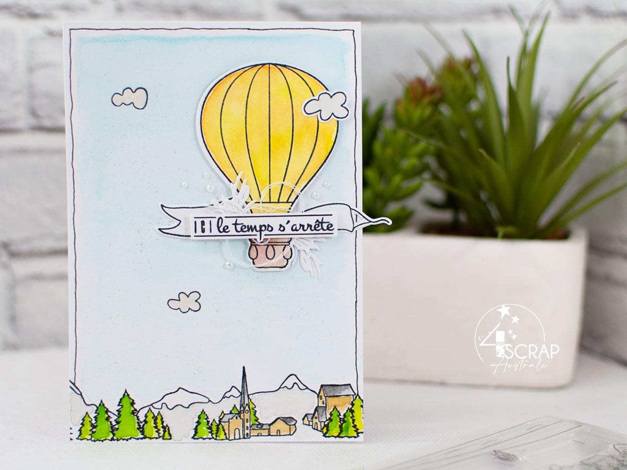 Carte avec fond paysage à l'aquarelle et une montgolfière assemblée à une étiquette, quelques feuillages, bannière et petits nuages.
