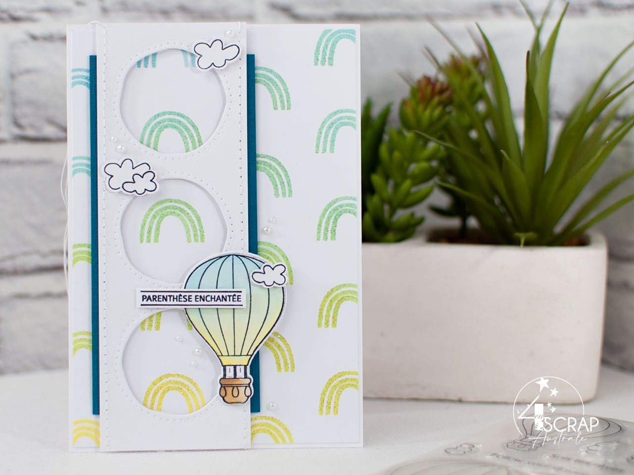 Création d'une carte avec un fond d'arc-en-ciel au pochoir et à l'encre distress, mongolfière colorisée à l'encre et quelques petits nuages blancs.