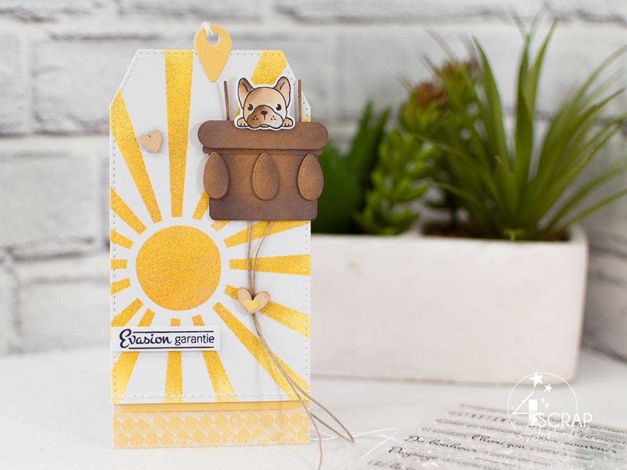 Création d'une étiquette à utiliser en marque-page avec fond soleil réalisé à l'encre et au pochoir, un petit bouli dans son panier de montgolfière et une étiquette.