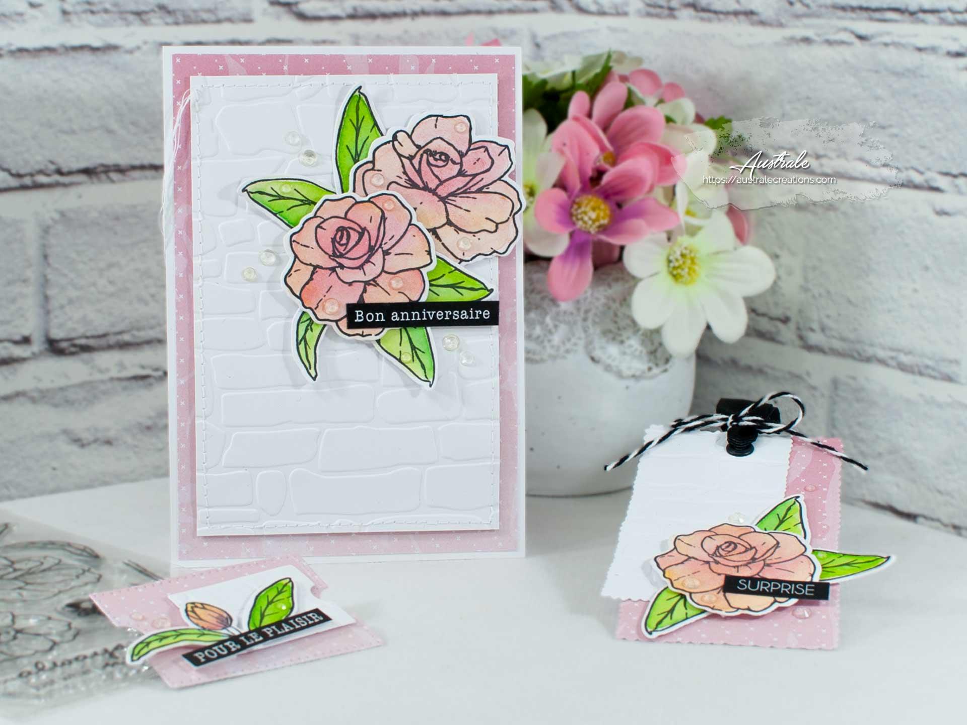 Création d'un ensemble pour cadeau d'anniversaire composé d'une carte et de deux étiquettes. Elles sont décorées de fleurs et feuillages mis en couleurs à l'aquarelle dans un combo en rose, blanc et vert.